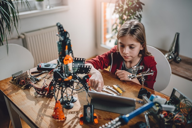 Girl building a robot at home