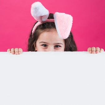 Girl in bunny ears hiding behind table