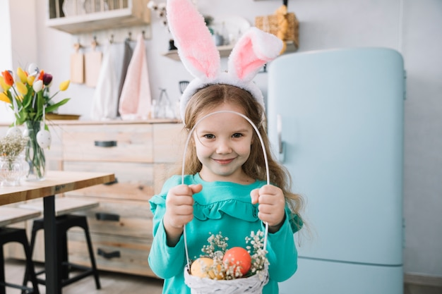 Girl in bunny ears holding basket with easter eggs