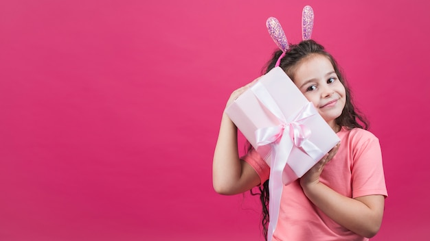 Girl in bunny ears holding gift box