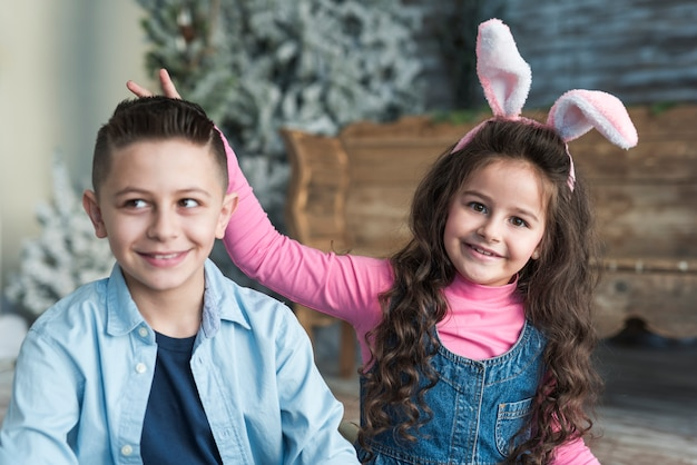 Girl in bunny ears making horns with fingers to boy