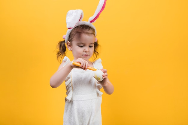 Girl in bunny ears painting egg with felt pen