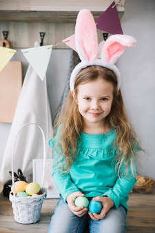 Girl in bunny ears sitting with basket of easter eggs