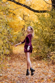 Girl in burgundy dress jumps in yellow autumn leaves