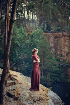 A girl in a burgundy long dress in a forest near the canyon. fabulous place.