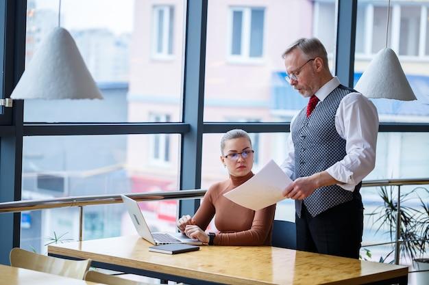 Девушка бизнес-леди, сидящая за деревянным столом с ноутбуком и работающий наставник босса учителя, указывает на свои ошибки. школа новой концепции развития бизнеса.