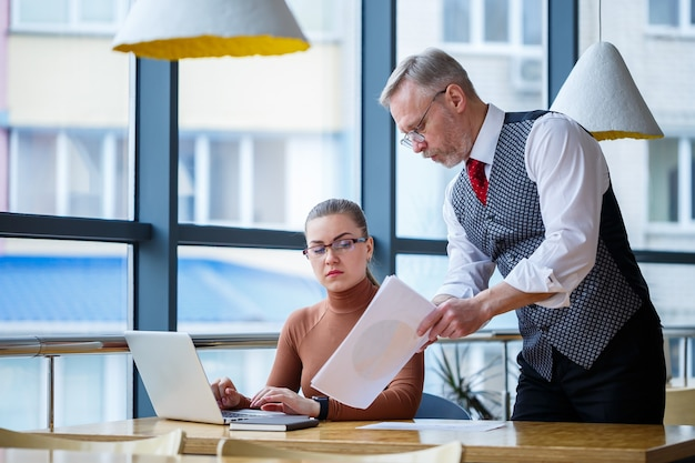 Girl business lady sitting at a wooden table with a laptop and working teacher boss mentor indicates her mistakes. school of a new business development concept.