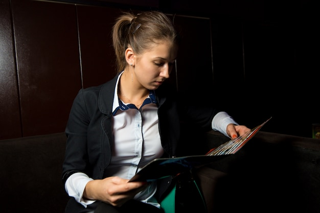 The girl in a business suit sits on the couch and reads the menu
