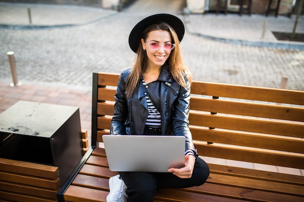 Девушка бизнес-леди сидит на деревянной скамейке в городе в парке осенью