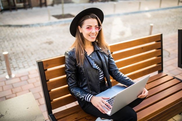 女の子のビジネス女性は秋の公園の街の木製のベンチに座る