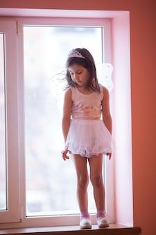 窓辺で遊んで踊る白いチュチュの女の子-蝶