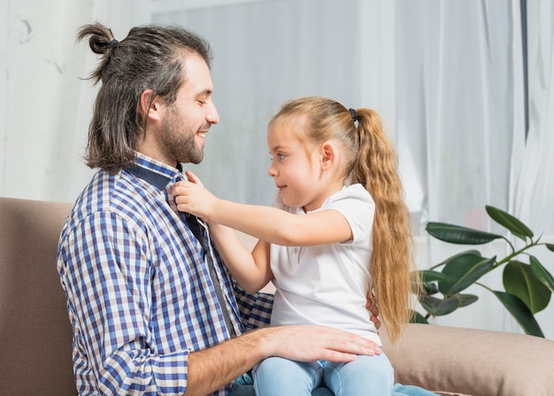 Girl buttoning her father's shirt