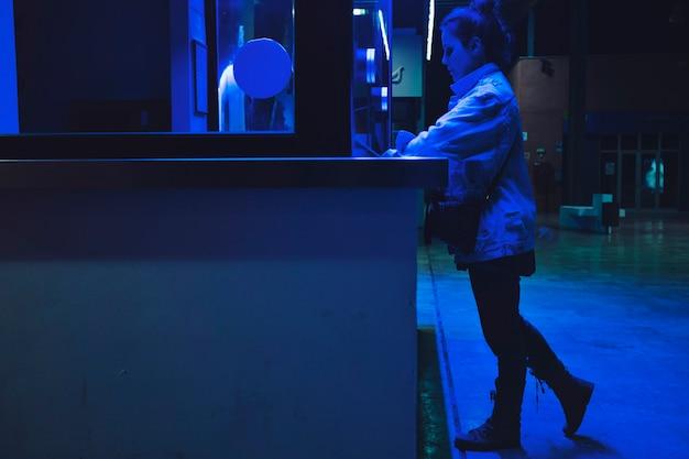 Ragazza che compra i ticchetti alla luce al neon