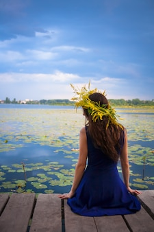 Girl by the lake with a wreath on head