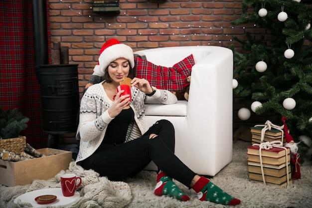 Девушка у рождественской елки в красной шляпе