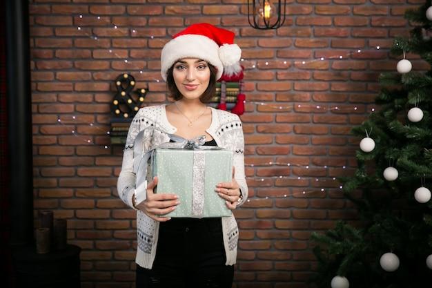 Девушка на рождественской елке распаковывает подарки