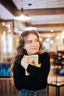 A girl in a cafe holding a book