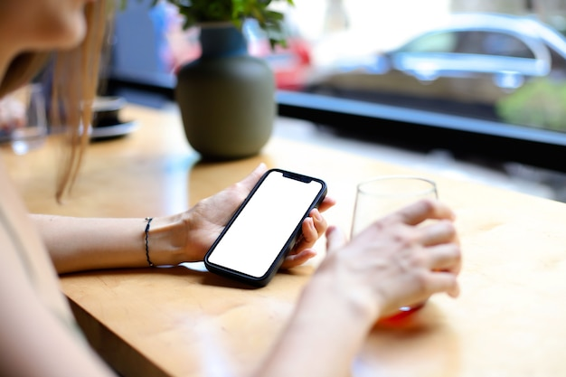Girl in cafe at the table holds a phone with blank screen in her hand. place for your design