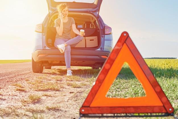 緊急一時停止の標識が付いている車の近くの助けを求める少女