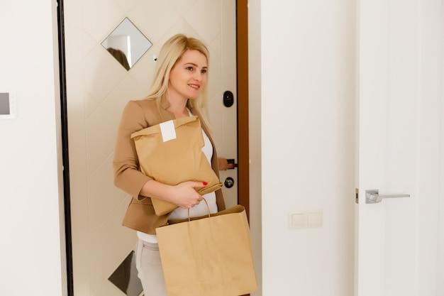 女の子は食べ物のパッケージを持って帰ってきました。食料品店から持ち帰った若い女性商品の購入。健康的な食事の概念。家のドアの背景に製品を持つ主婦