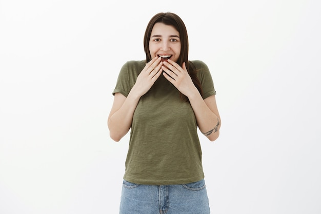 Girl cannot believe she received such awesome gift gasping smiling broadly and holding palms over mouth from amazement and joy reacting to cool surprise delighted and impressed over gray wall