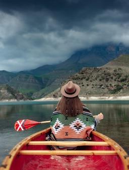 曇りの日に山の湖でカヌーをする女の子bylym湖の不機嫌そうな雰囲気