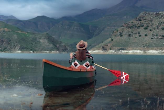 ギシュギット湖の曇りの日の不機嫌そうな雰囲気の山の湖でカヌーをする女の子