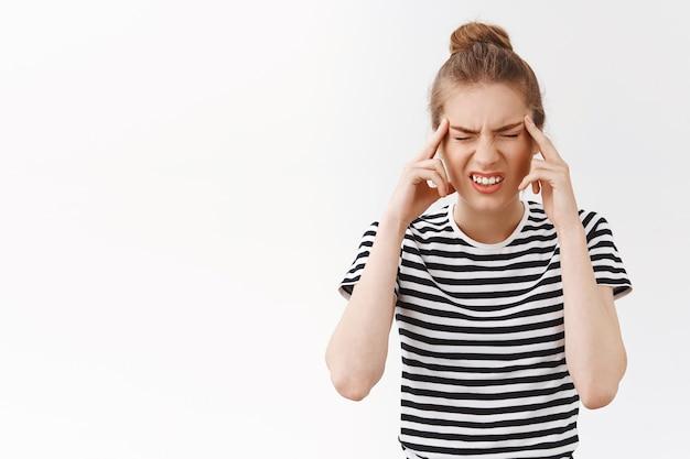 소녀는 집중할 수 없고, 두통이 심하고, 편두통이 있고, 고통으로 눈을 가늘게 뜨고 이를 악물고, 관자놀이를 만지고, 아프고, 서 있는 흰색 배경이 고통스러운 질병을 괴롭힙니다.
