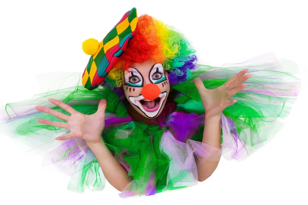 Girl in cap and clown costume with a bouquet of flowers puts out the tongue looks up isolated