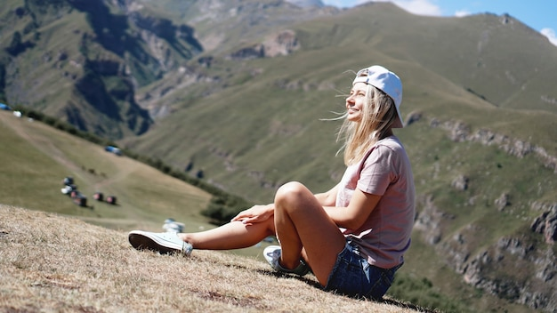 The girl in a cap and shorts in the mountains sits on the grass