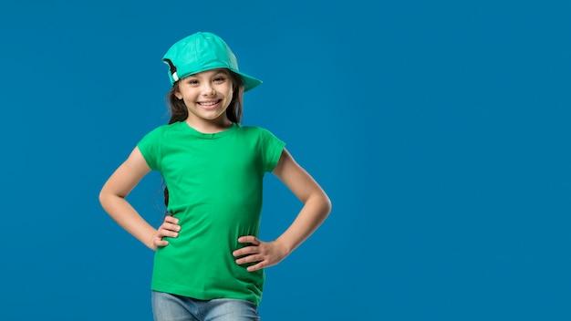 Girl in cap standing in studio