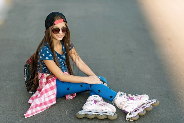 A girl in a cap and sunglasses on rollers is resting while sitting on the road