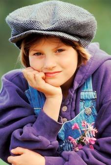 Girl in cap and sweatshirt with head in hands