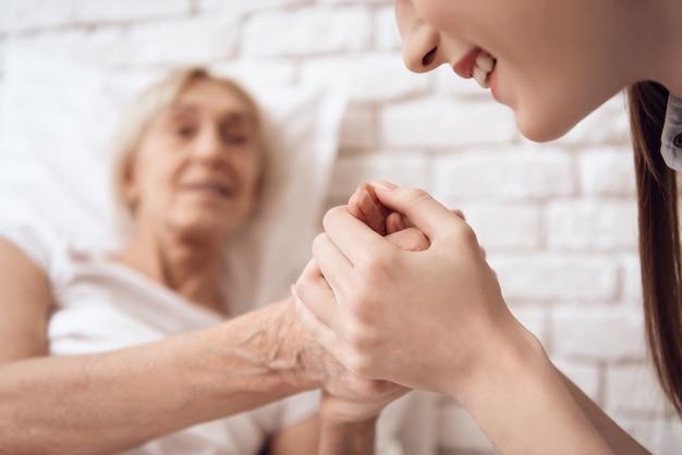 自宅のベッドで女の子介護高齢女性