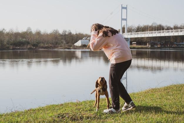 Девушка ласкает брошенную собаку на берегу озера. приемные животные. поти, грузия.