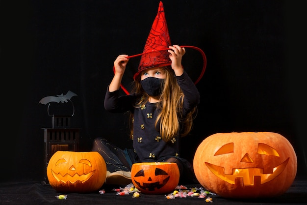 A girl in a carnival costume of witch and a medical mask on plays with pumpkins and sweets