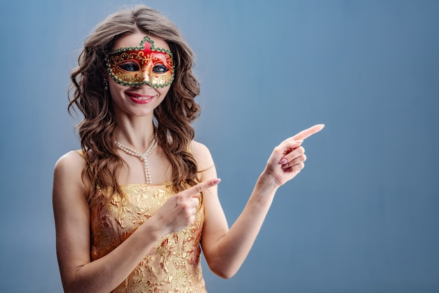 The girl in the carnival mask is smiling while standing and pointing to the side