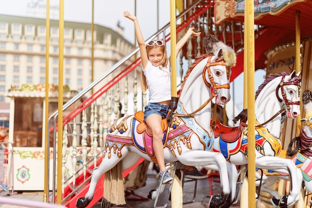 Girl in a carousel with horses at a fair