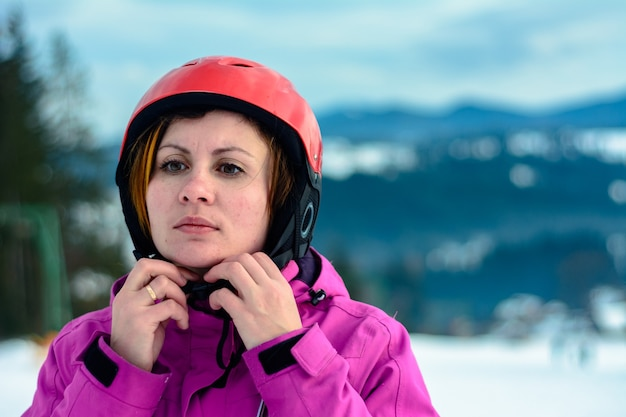 Girl in the carpathians in a purple jacket and red helmet.