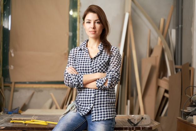 Girl carpenter in checkered shirt with arms crossed in workshop