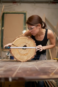 Girl carpenter with tape measure and saw cut tree in her hands in workshop