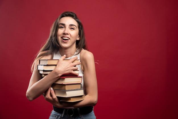 La ragazza trasporta una pesante pila di libri