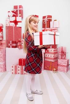Девушка несет тяжелый рождественский подарок