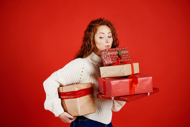Girl carrying a stack of christmas presents