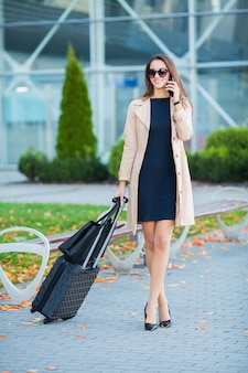 Girl carrying suitcase by streets. smiling blond businesswoman with wheeled luggage