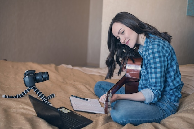 Girl in casual clothes on the bed, records music blog and plays acoustic guitar