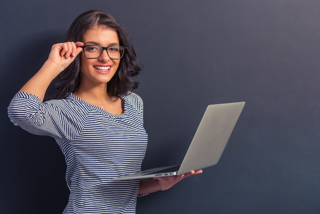 Girl in casual clothes and eyeglasses is holding a laptop.