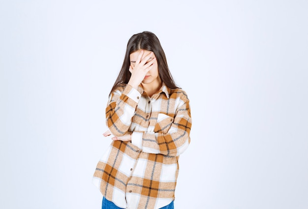 Girl in casual clothes holding her face on white wall.