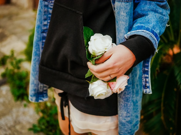 Girl in casual jeans jacket and black hoodie holding a bouquet of white and pink roses flowers. selective focus. flower delivery concept