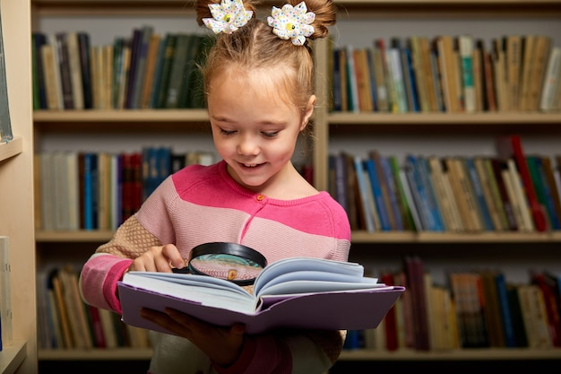 Girl in casual wear in library after school, reading an encyclopedia,diligent child use magnifying glass
